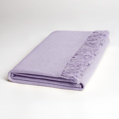 A folded, long, lilac-colored cashmere scarf with fringes on both ends on a white background.