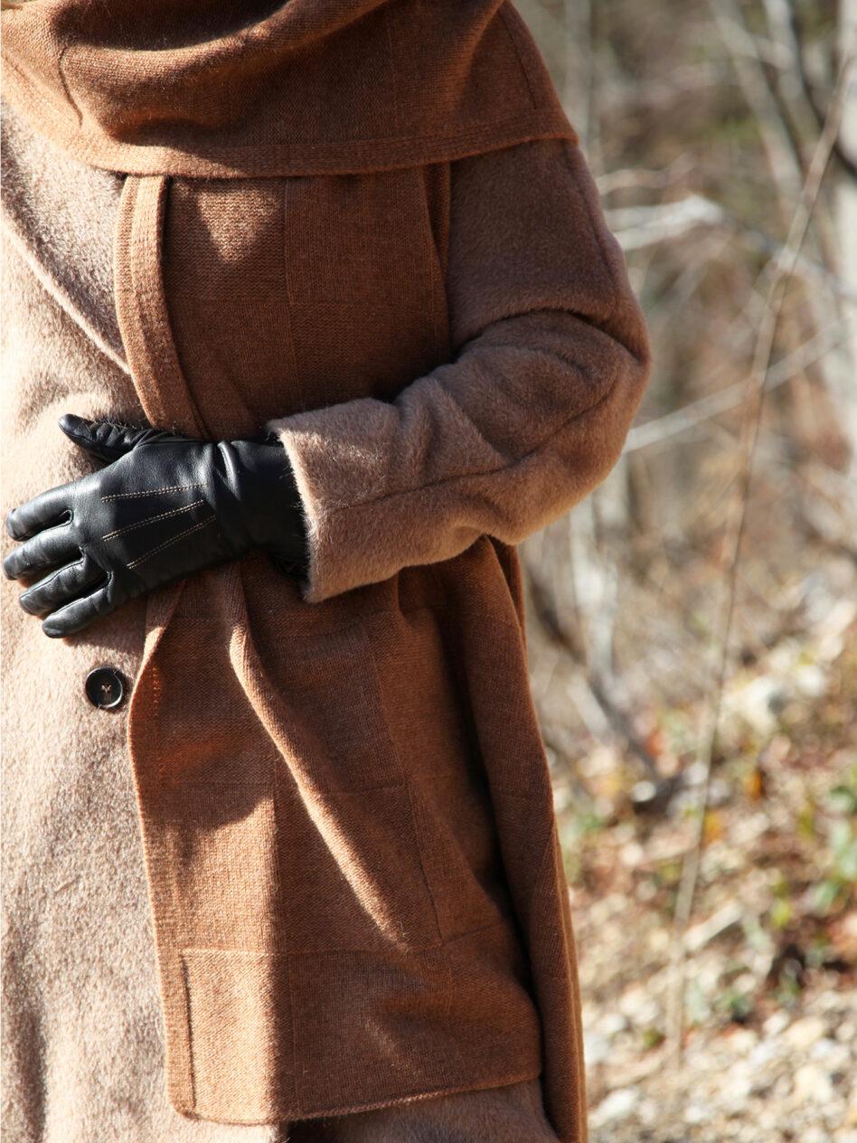 Eine Frau mit schwarzen Lederhandschuhen und trendigem braunen Wintermantel trägt den Kaschmirschal BERLIN von EMAAL in der Farbe Haselnuss locker gebunden.