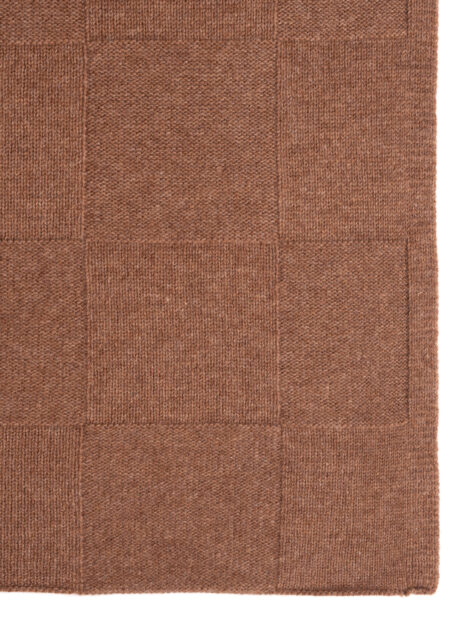 The knitted scarf BERLIN with large checks in the color hazelnut is seen in a detail shot against a white background. The large checkerboard pattern of fine cashmere comes into its own here.