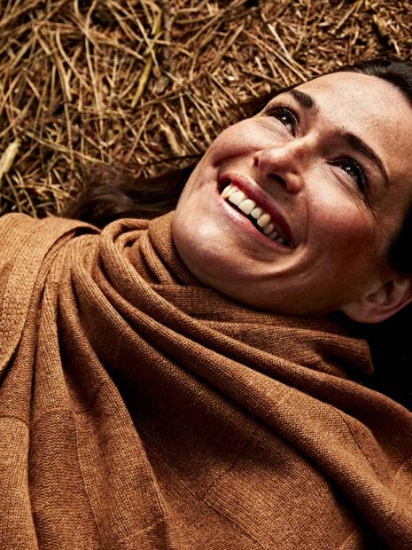 Eine dunkelhaarige Frau liegt auf dem Boden und trägt den Kaschmirschal Berlin von Emaal in der Farbe Haselnuss. Das grosse Karomuster des Schals ist im Detail abgebildet.