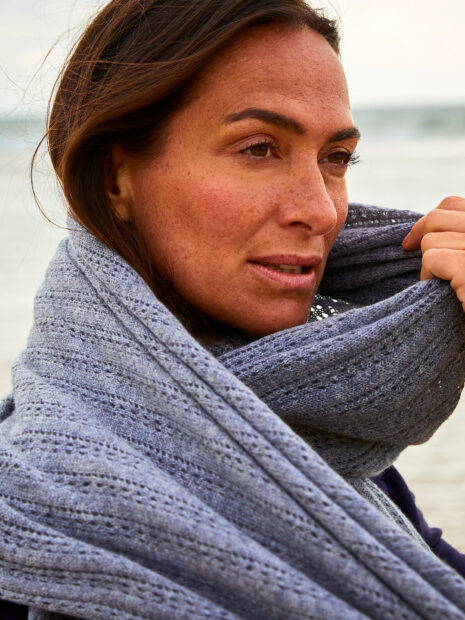 The model Sandra Blesser wears the cozy cashmere scarf Lhasa in the color husky several times loosely tied around the neck on the beach of Sylt. The hole pattern of this scarf made of 100% cashmere is particularly well visible. Loosely knitted, the cozy cashmere yarn gives this scarf a folkloric touch and keeps you nice and warm on this cool beach day. The gray pattern scarf forms a harmonious contrast to her dark brown hair and tanned face.