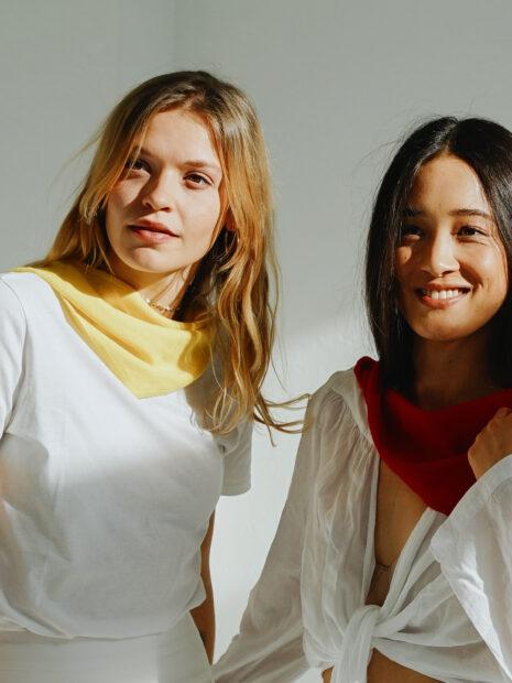 New York, das kleine Halsdreieck aus Kaschmir wird von einem jungen Mann in der Farbe Husky locker um den Hals getragen. Eine Frau schmiegt sich an den Mann und trägt das Modell New York in der Farbe Creme. Die beiden tragen weisse Kleidung.