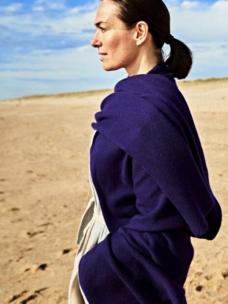 Der oversize Kaschirschal Oslo in der Farbe acai ist über die linke Schulter des Models Sandra Blesser geworfen. Dadurch kommt das Muster des Schals gut zur Geltung. Der kuschelige Schal aus 100% Cashmere bildet einen guten Kontrast zum hellgrauen Mantel des Models. Die dunkelhaarige Frau steht am Strand von Sylt.
