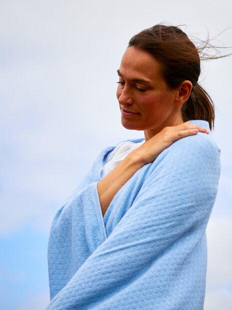 Eine junge brünette Frau ist in einer Nahaufnahme vor dem blaumem Himmel auf der Insel Sylt zu sehen. Sie hat sich den gemusterten, großen Schal Isfahan von EMAAL Cashmere aus 100 % Kaschmir in der Farbe hellblau übergeworfen und wärmt sich damit. Sie guckt verträumt und berührt dabei das weiche, kuschelige Kaschmirgarn des Musterschals. Das wunderschöne Muster ist gut zu sehen und erinnert an die außergewöhnliche Architektur der eindrucksvollen und farbintensiven Bauten Isfahans, dem Namensgeber dieses Kaschmirschals.