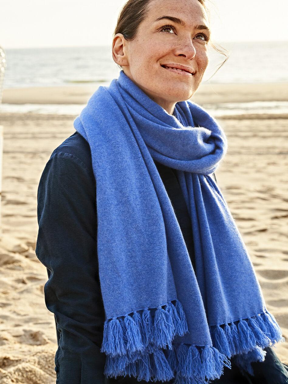 Den Kaschmirschal MILANO mit den langen Fransen in der Farbe jeansblau trägt das Model am Strand von Sylt locker um den Hals. Der oversize Schal bildet einen tollen Kontrast zu ihrer dunkelblauen Jacke. Im Hintergrund ist das Meer und der Strand zu sehen.