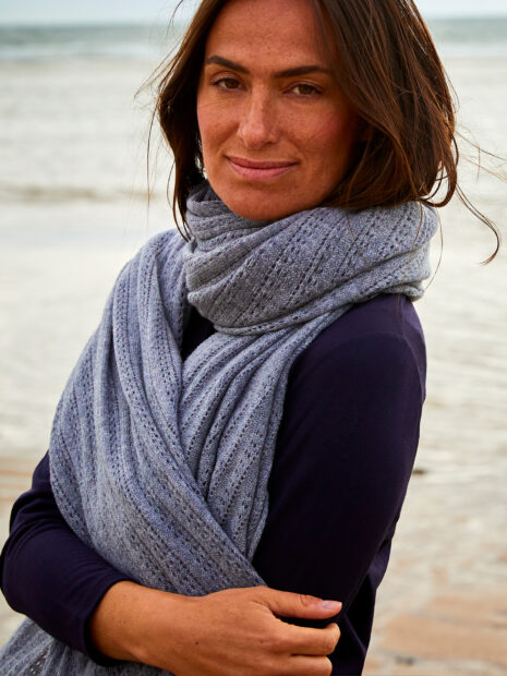 The model Sandra Blesser presents the cashmere scarf Lhasa in the color husky loosely tied around the neck on the beach of Sylt. Loosely knitted, the cozy cashmere yarn gives this scarf a folkloric touch and keeps you nice and warm. The gray pattern scarf forms a harmonious contrast to her dark blue cotton blouse. The hole pattern of this 100% cashmere scarf is particularly well seen.