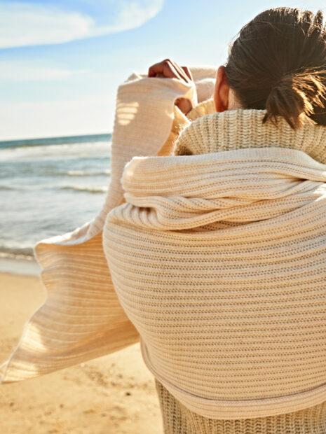 Am Strand von Sylt blickt eine Frau aufs Meer und trägt den Kaschmirschal LIMA in der Farbe Champagner. Sie hält ein Ende des gemusterten Strickschals in einer Hand. Der Schal ist um ihren Rücken gebunden und so sieht man das Muster des Schals im Detail. Zum Schal trägt sie einen cremefarbenen grob gestrickten Cadigan mit Rollkragen.