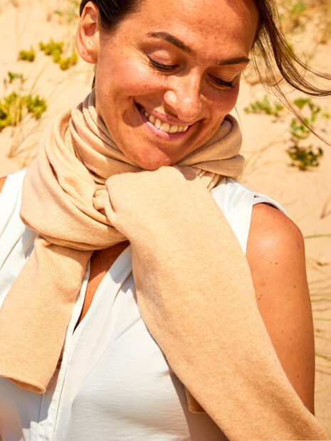 A young woman with brown hair sits in the dunes on the beach of Sylt and lets the sun shine on her. She wears the classic knitted scarf LONDON by Emaal made of 100% cashmere in the color cappuccino as an accessory to a white sleeveless summer blouse. The scarf is loosely knotted around the neck. The straight shape of this light summer scarf perfectly hides the neckline at the neck. An absolute classic for ladies and gentlemen.