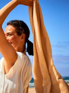 Eine junge Frau mit braunen Haaren läuft am Strand von Sylt und trägt eine weisse ärmellosen Sommerbluse. Der Himmel ist strahlend blau und sie hält den sommerlich, leichten, klassischen Schal LONDON von Emaal Cashmere in der Farbe Cappuccino im Wind wehen. Ein Sommerschal mit klassischer Strickung.