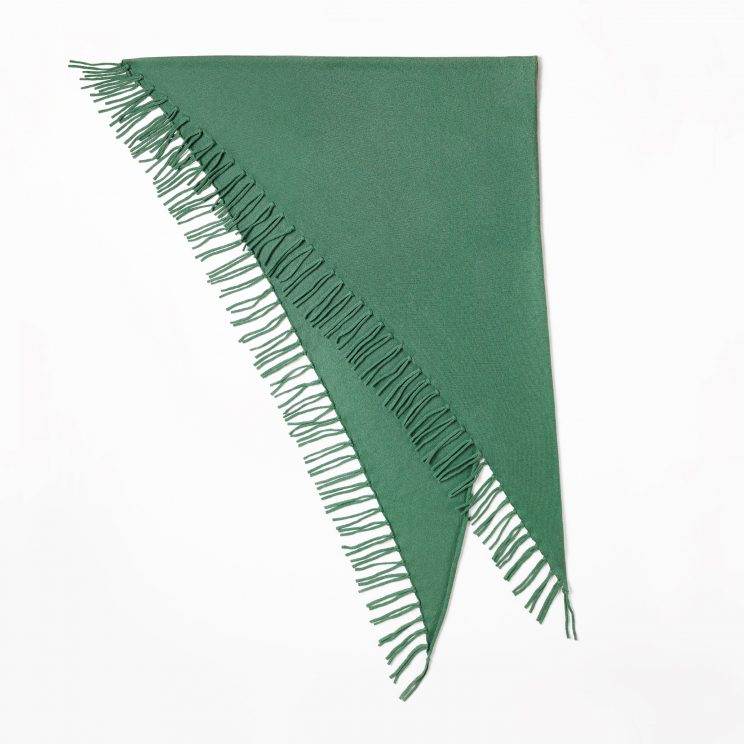 A folded, large cashmere triangle scarf with long fringes in the colour salvia on a white background.