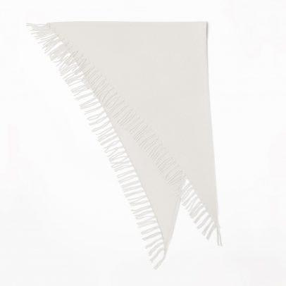 Ein gefaltetes, grosses Cashmere Dreieckstuch mit langen Fransen in der Farbe Kreide auf weissem Hintergrund.