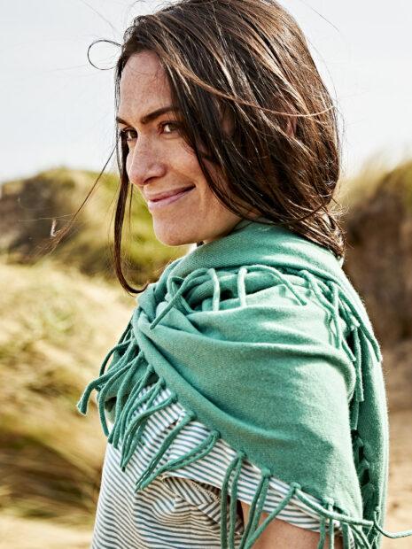 Eine dunkelhaarige Frau trägt am Strand von Sylt den Kaschmirschal Los Angeles in der Farbe Salbei sehr locker um den Hals und Schultern geschlungen. Man kann gut sehen wie die langen Fransen des sommerlich, leichten Kaschmirdreiecks am Schal verknotet sind. Zum Kaschmirschal trägt das Model Sandra Blesser ein grün-weiss gestreiftes sommerliches T-Shirt. Im Hintergrund ist eine Dühne zu sehen.
