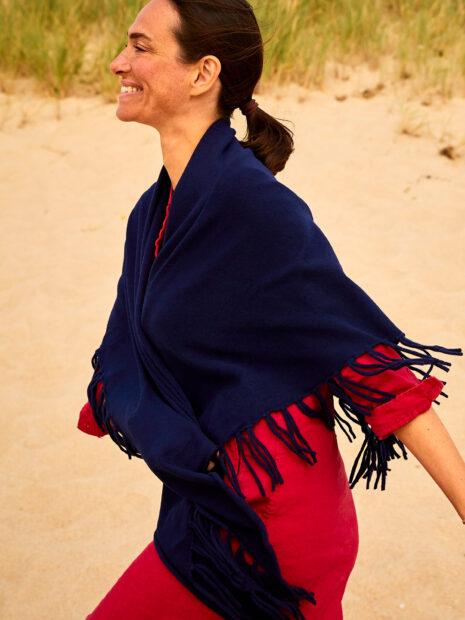 Eine dunkelhaarige Frau hat sich den Kaschmirschal Los Angeles in der Farbe Navy sehr locker umgebunden und läuft am Strand entlang. Die langen Fransen des sommerlich, leichten Kaschmirdreiecks sind am Tuch verknotet und wehen im Wind. Das Model Sandra Blesser trägt ein sommerliches knallrotes Blusenkleid, das farblich gut zum Schal passt und einen tollen Kontrast bildet. Im Hintergrund der Sandstrand von Sylt.