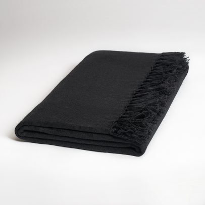 A folded, long, black cashmere scarf with fringes on both ends on a white background.