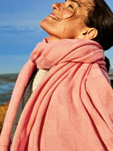 Eine dunkelhaarige Frau genießt die Sonne am Strand von Sylt und trägt den Kaschmirschal MOSKAU mit großem Karo-Strickmuster locker um den Hals. Der lange Schal fällt locker über ihre Schulterch und das große Karo-Muster kommt gut zur Geltung.