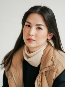 New York, das kleine Halsdreieck in der Farbe Creme wird von einer jungen Frau mit schwarzem Pullover und einer oversize Dauenweste locker um den Hals geknotet getragen.