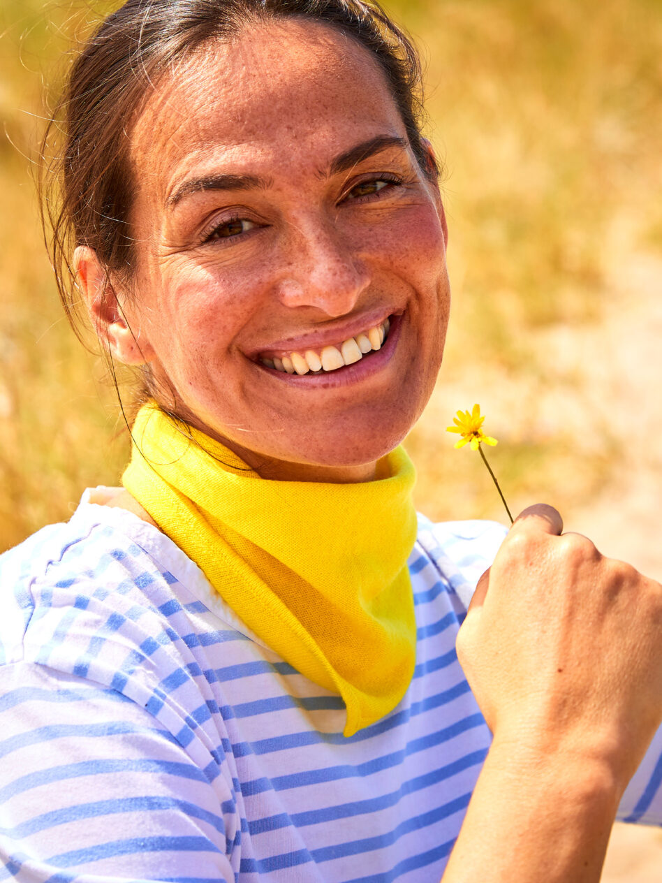 Locker am Hals verknotet passt New York, das trendige Halsdreieck aus 100 % Kaschmir in der knalligen Farbe gelb, perfekt zum Ausschnitt ihres maritimen, hellblau gestreiften T-Shirt. Der kleine Dreiecks-Schal verleiht dem brünetten Modell Sandra Blesser,, das in den Dünen von Sylt in die Sonne lacht und dabei an einer Blume schnuppert, eine persönliche Note. Das Tuch ist locker-leicht und liegt dennoch eng genug am Hals an, um bei einer frischen Frühlingsbrise warm zu halten.