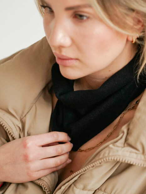 New York, the small triangle shaped scarf is worn loosely around the neck by a young woman. It is loosely knotted.
