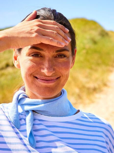 Locker am Hals verknotet passt New York, das kleine Halsdreieck aus 100 % Kaschmir, perfekt zum Ausschnitt ihres maritimen, hellblau gestreiften, sommerlichen T-Shirt und verleiht dem brünetten Modell eine persönliche Note. Das Tuch ist locker-leicht und liegt dennoch eng genug am Hals an, um bei einer frischen Frühlingsbrise warm zu halten.