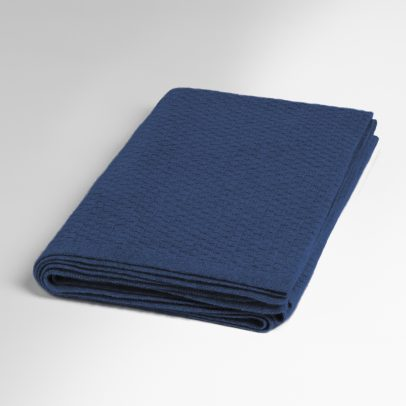 The patterned cashmere scarf in the colour navy from the new EMAAL collection lies folded on a white background.