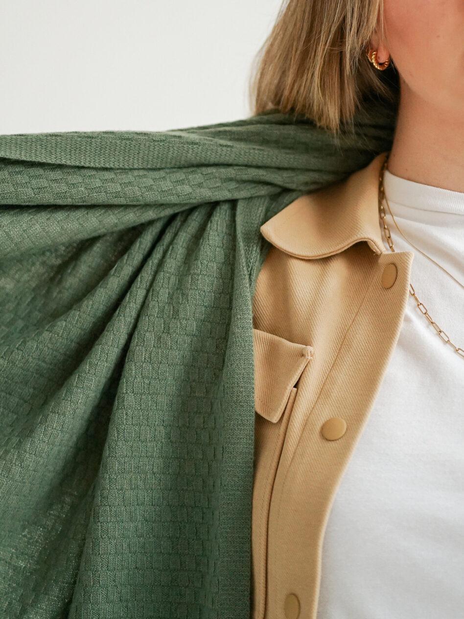 Das Muster des Strickschals SYLT von EMAAL Cashmere kommt gut zur Geltung, da das blonde Modell den olivgrünen Schal um die rechte Schulter trägt und das Ende in einer Hand hält