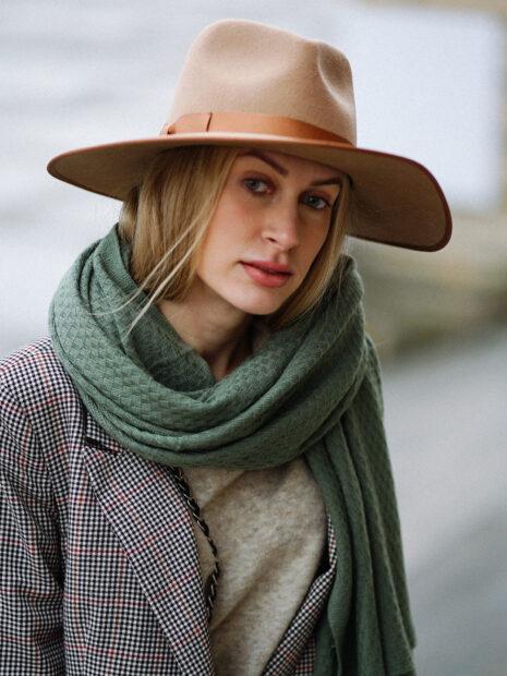 Frau mit Hut trägt den langen Kaschmirschal SYLT von EMAAL Cashmere locker um den Hals gelegt. Der olivgrüne Schal passt sehr gut zu ihren blonden Haaren.